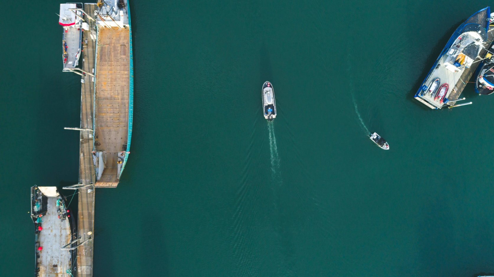 Aerial photograph of a boat gliding through the ocean next a tanker
