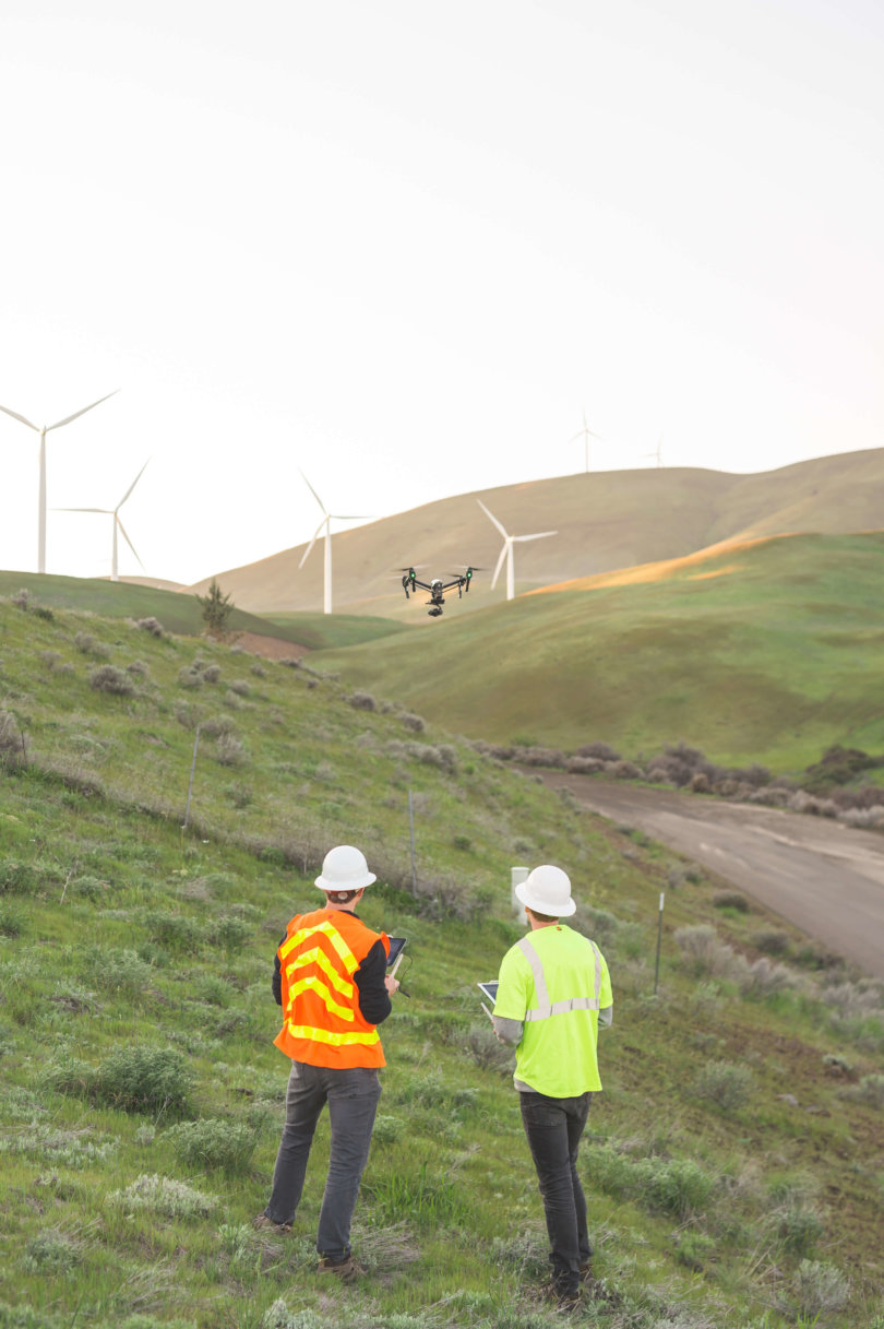 Photograph of two men flying a drone around wind turbines in Oregon